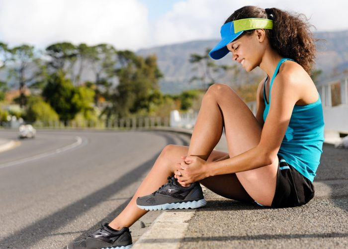 woman in running gear sitting on a roadside curb holding onto her ankle in pain