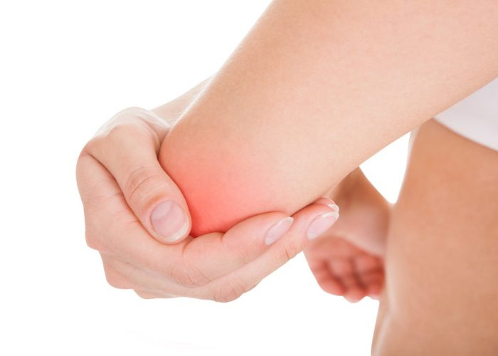 woman holding her strained elbow caused by a gym injury