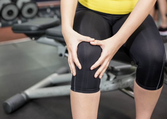 woman holding onto her knee gym injury