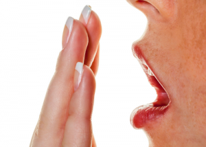 woman blowing onto the palm of her hand to smell her breath