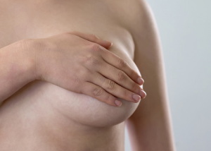 woman holding onto her left breast to give herself a self breast examination