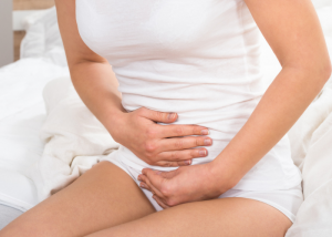 woman holding onto her belly in pain due to being constipated