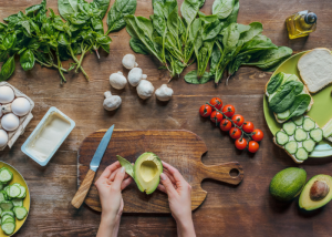 woman with a chopped half of an avocado on a wooden board, and other vegetables around it like garlic, leafy greens, tomatoes