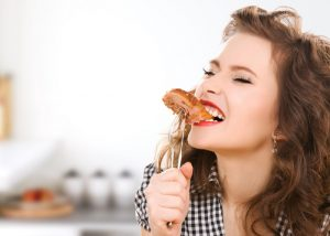 woman biting into a piece of meat on a fork in her kitchen