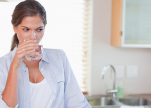 woman drinking a glass of water in her kitchen to stay hydrated