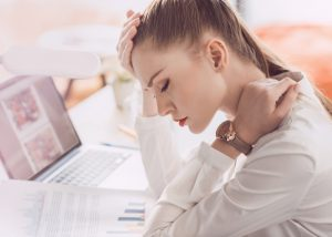 woman at her work desk with eyes closed looking tired
