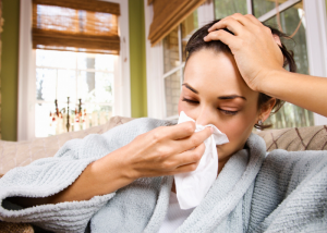 woman with the flu in a robe on her sofa blowing her nose