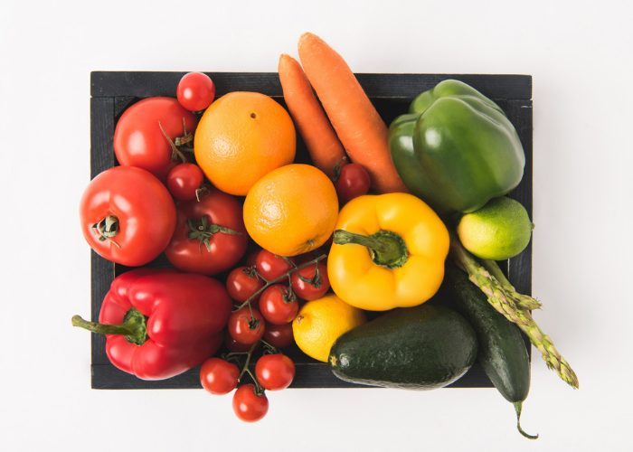 a basket full of fresh vegetables like peppers, tomatoes, carrots, eggplant, asparagus, cucumbers