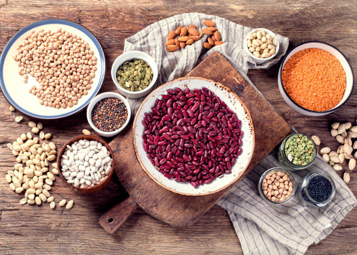 protein rich legumes such as chickpeas, kidney beans, and soy beans laid out on a wooden table