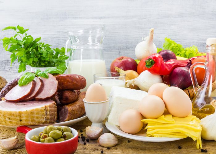 a spread of high protein meat and dairy food products like eggs, milk, and meat laid out on a table