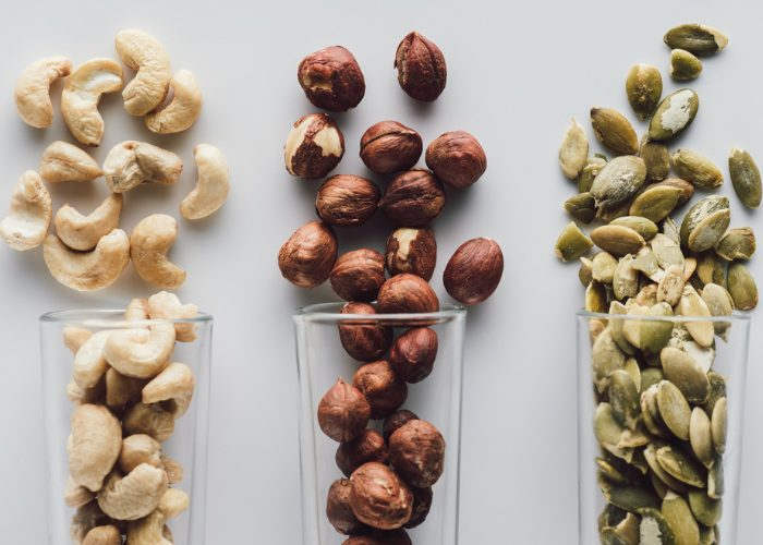 protein rich cashews, pistachios and macadamia nuts lined up on a table