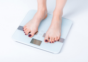 woman standing on electronic weight scale to measure how much she weighs