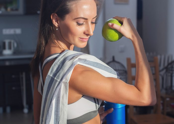 woman holding a green apple and flexing her biceps