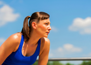 woman with a ponytail in a blue tank top getting ready to run