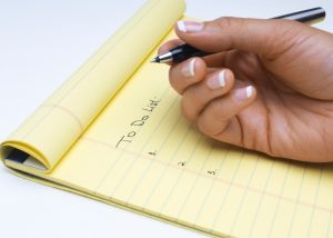 woman holding a black pen with a yellow notepad writing a to do list
