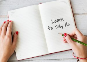 "woman holding a green pencil with an open notebook that is opened to a page that says ""learn to say no"""