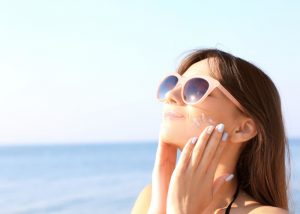 woman with sunglasses at the beach applying sunscreen on her face