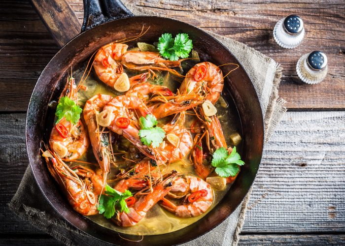 stir fried prawns with garlic, chili, and parsley in a skillet