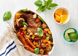 an oven dish filled with meat and roasted vegetables, topped with basil leaves and citrus fruits on the side for zest