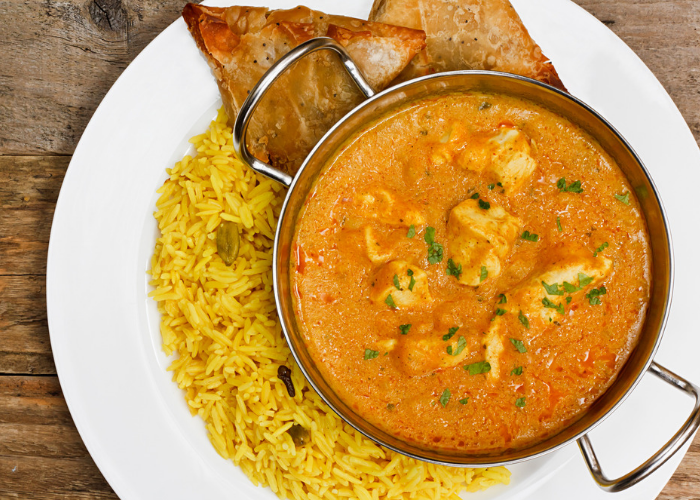 chicken korma curry in a silver dish on a white plate, with sides of yellow rice and samosas