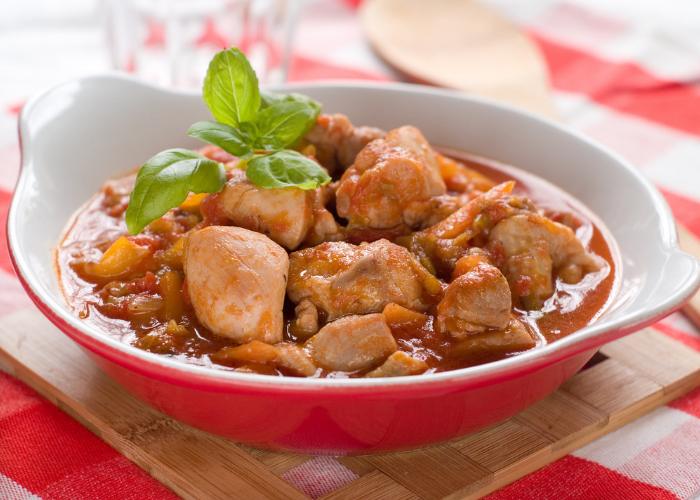 One pot flaming chicken stew topped with a sprig of fresh basil on a red dish