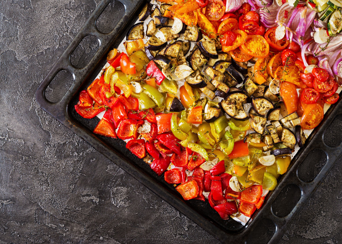 one pot meal of roasted peppers, eggplant, tomatoes, onions, and zucchini on an oven tray