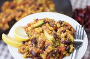 One pot vegan mexican quinoa plated on a white dish with lemon wedges on the side