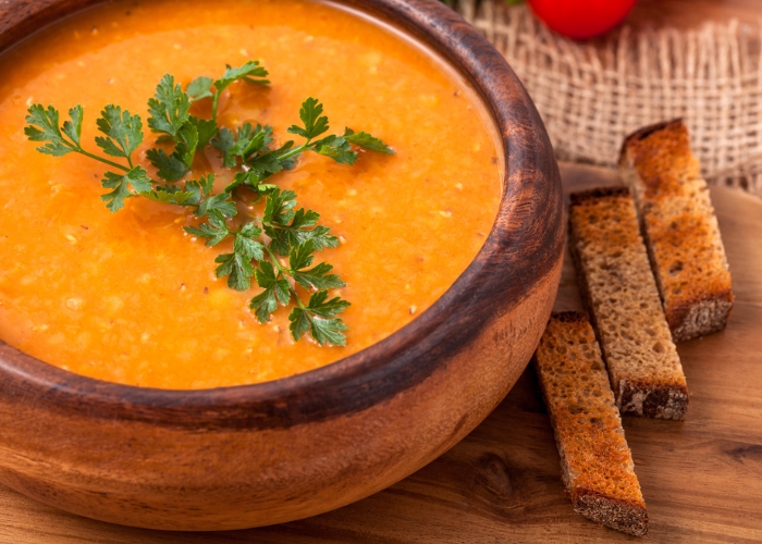 a bowl of orange carrot lentil soup topped with parsley, and 3 toasted breadsticks on the side