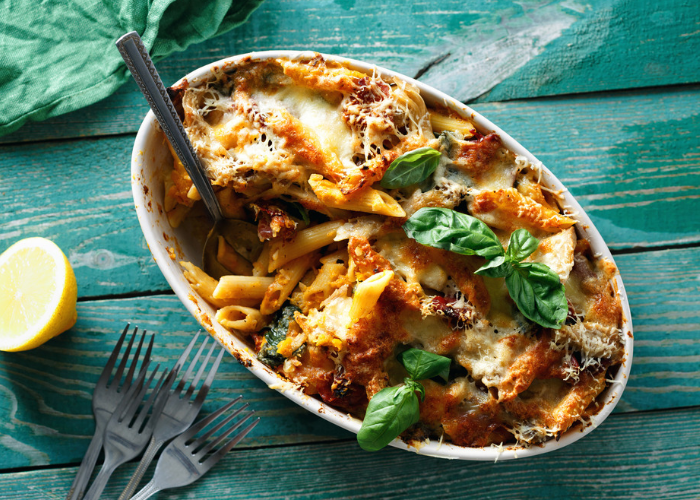 Pasta bake topped with fresh green basil in an oven dish, with four forks and a lemon wedge on a green wooden table