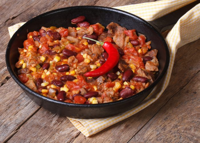 Homemade vegetarian, meat-free chili in a skillet, topped with a whole fresh red chili pepper