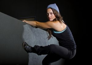 female parkour artist climbing a wall at night