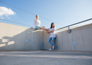 two women on a rooftop, one sitting on the edge of a wall and the other standing beside her friend