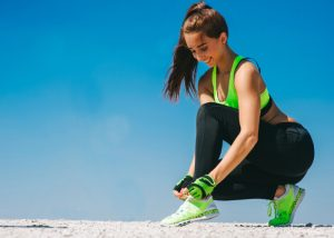 parkour woman dressed in neon green sports bra, black pants, green shoes, and green parkour gloves tying her shoelace