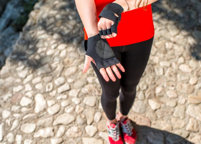 Woman in red fitness top and red shoes putting on parkour gloves