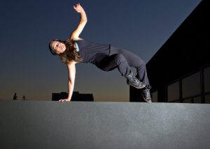 woman doing parkour jumping over a wall