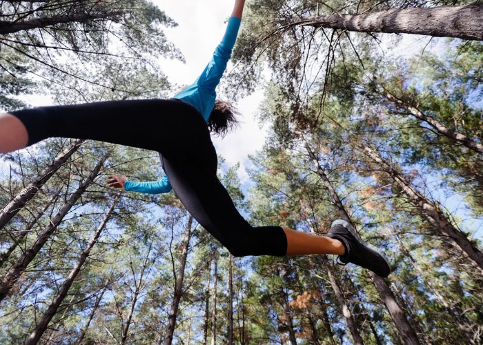 Bottom to top view of woman doing parkour training jumping across an obstacle in the woods surrounded by tall trees