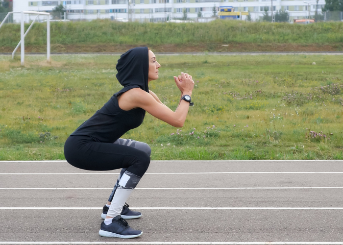 Woman in black hoodie in squatting position getting ready to do a high jump