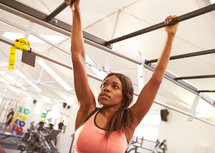 Woman at the gym doing parkour training on monkey bars