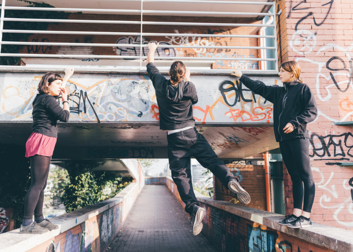 3 young women practicing parkour in their neighbourhood with graffiti walls