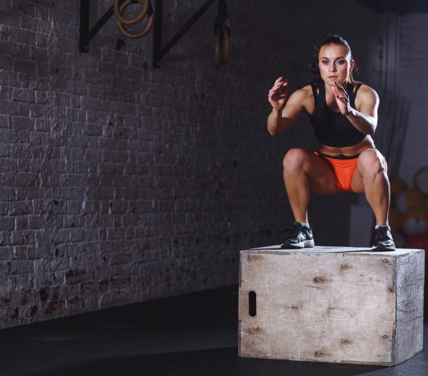 Woman in black top and orange shorts doing box jump plyometric exercises at the gym