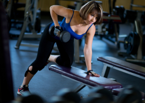 woman working out her biceps with weights at the gym