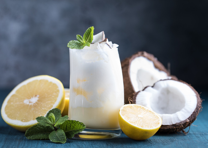 a glass of coconut smoothie with fresh coconut, lemons and mint leaves around it.