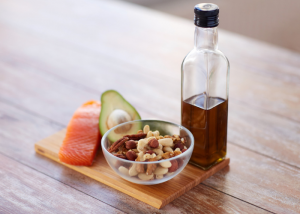 a portion of fresh salmon, half an avocado, nuts in a bowl and olive oil on a wooden board