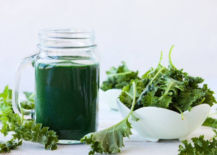 a green mason jar cup of green smoothie with a bowl of kale leaves next to it and kale leaves scattered around