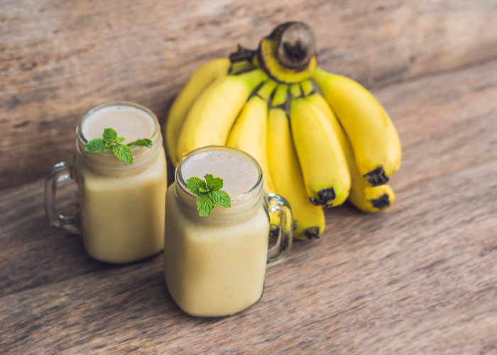 two mason jar glasses of banana oat smoothies, garnished with sprigs of mint, and a bunch of bananas set behind them on a wooden table
