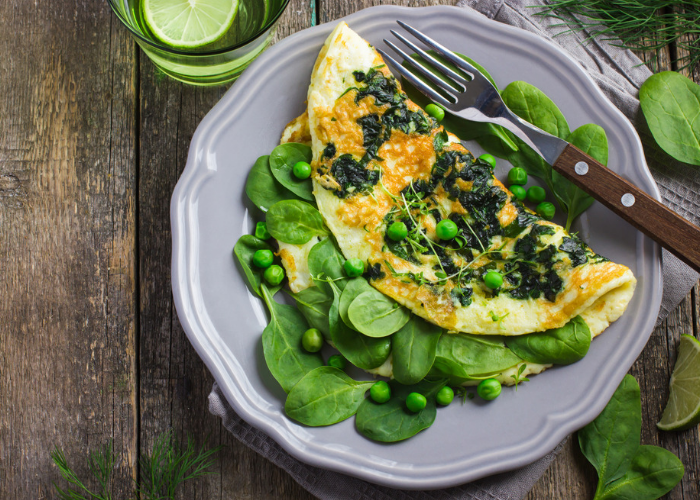 a superfood omelet of eggs, spinach and green peas on a purple plate