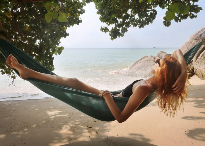 woman lyying on a hammock by the beach under the shade to protect her skin from sun damage