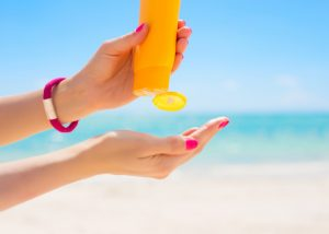 woman squeezing sunscreen out onto her hand at the beach