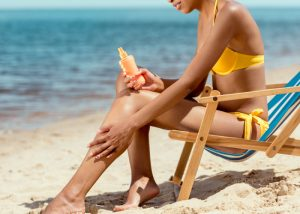 woman in a yellow bikini at the beach, sat on a beach chair, and applying sunscreen on her legs