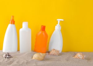 bottles of sunscreen placed in sand against a yellow wall with sea shells scattered around